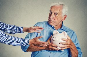Senior man holding piggybank